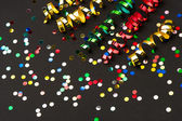 Colorful streamer and confetti on black paper background — Stock Photo