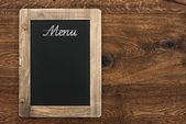 Vintage blackboard on wooden background — Stock Photo