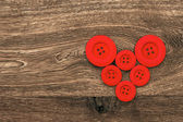 Red buttons shaped heart over wooden background — Stock Photo