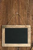 Vintage blackboard hanging on wooden wall — Stock Photo