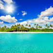 Tropical island beach with sunny blue sky - Stock Photo