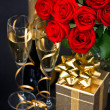 Red roses, golden gift and and champagne — Stock Photo