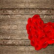 Heart shaped red rose petals on wooden background — Stock Photo #21840927
