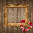 Old golden frame with roses over wooden background — Stock fotografie