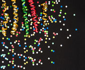 Colorful streamer and confetti on black paper — Stock Photo