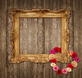 Old golden frame with roses over wooden background — Stock Photo
