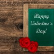 Vintage green blackboard with red roses — Stock Photo