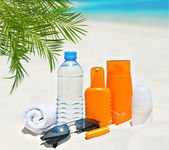 Water and sun protection cream on beach background — Stock Photo