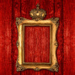 Royalty-Free Stock Photo: Golden frame with crown over red wooden background