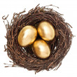 Foto Stock: Golden easter eggs in nest isolated on white