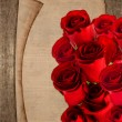 Stock Photo: Bouquet of red roses and vintage paper sheet