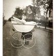 Mother with baby in vintage buggy — Stock Photo #21905801