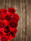 Bouquet of red roses over wooden background — Stock Photo