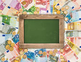 Euro coins and banknotes background with green chalkboard — Stock Photo