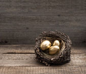 Golden easter eggs on wooden background — Stock Photo
