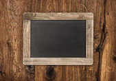 Vintage blackboard on wooden wall — Stock Photo