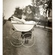 Mother with baby in vintage buggy — Stock Photo