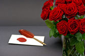 Bouquet of red roses and love letter on black — Stock Photo