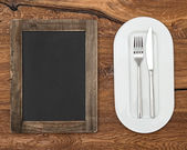 Blackboard for menu on wooden table — Stock Photo