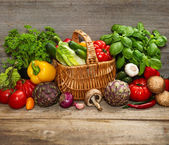Vegetables and herbs on wooden background — Stock Photo