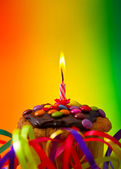 Birthday cupcake with festive decoration and candle — Stock Photo