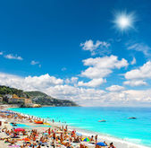 Tourists, sunbeds and umbrellas on sunny hot day — Stock Photo