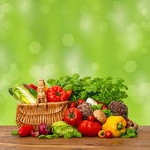 Fresh vegetables and herbs over green background — Stock Photo