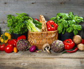 Fresh herbs and vegetables on wooden background — Stock Photo