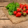 Fresh strawberries with mint leaves on wooden background — Stock Photo