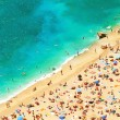 Beach with tourists, sunbeds and umbrellas. holidays background — Stock Photo #28710731