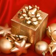 Gift box with golden christmas balls on red silk — Stock Photo