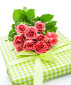 Fresh pink roses with gift isolated on white — Stockfoto