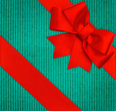 Red ribbon bow over blue recycled cardboard — Stock Photo