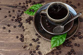 Cup of black coffee with beans and leaves — Stock Photo