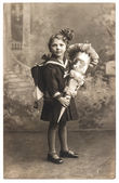 Vintage sepia portrait of a first grader school girl with school — Stock Photo