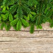 Fresh christmas tree branch over wooden background — Stock Photo
