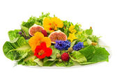 Green salad with flowers and fruits — Stock Photo