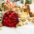 Christmas decoration with red baubles und golden gift box — Stock Photo