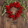 Christmas tree branches and red wreath on wooden — Stock Photo