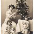 Mother and children with christmas tree wearing vintage clothing — Stock Photo