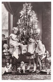 Happy kids with christmas tree, gifts and vintage toys — Stock Photo
