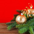 Golden christmas balls with christmas tree branch on red — Stock Photo