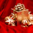 Stock Photo: Gift box with golden christmas baubles decoration