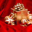 Gift box with golden christmas baubles decoration — Stock Photo #36318669