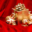 Stock Photo: Gift box with golden christmas balls and shiny lights