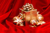 Gift box with golden christmas baubles decoration — Stock Photo