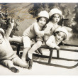 Stock Photo: Old photo of kids with sledge. vintage christmas postcard