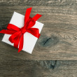 White gift box with red ribbon bow on wooden background — Stock Photo #36323617
