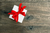 White gift box with red ribbon bow on wooden background — 图库照片