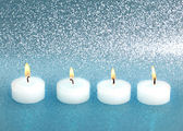 Burning candles over silver blue shiny background — Stock Photo